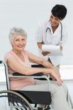 Docteur féminin parlant à un patient supérieur dans le fauteuil roulant Photographie stock libre de droits