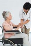 Docteur féminin parlant à un patient supérieur dans le fauteuil roulant Photo stock