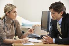 Docteur féminin parlant au patient d'homme d'affaires photos stock