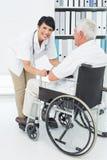 Docteur féminin parlant au patient supérieur dans le fauteuil roulant Photographie stock