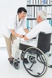 Docteur féminin parlant au patient supérieur dans le fauteuil roulant Images libres de droits