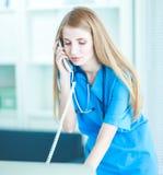Docteur féminin parlant au téléphone au centre de diagnostic Image stock