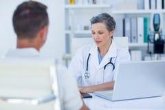 Docteur féminin parlant avec son patient Photos stock