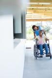 Docteur féminin poussant le patient supérieur heureux dans le fauteuil roulant Image stock