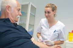 Docteur féminin prenant le sang à l'aîné à la maison de repos Images stock