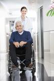 Docteur féminin Pushing Senior Patient dans le fauteuil roulant Image stock