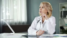 Docteur féminin réfléchi s'asseyant à la table, analysant des résultats patients, diagnostic photo libre de droits