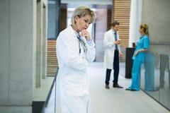 Docteur féminin réfléchi tenant le couloir de n photos libres de droits