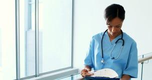 Docteur féminin regardant le presse-papiers dans le couloir clips vidéos