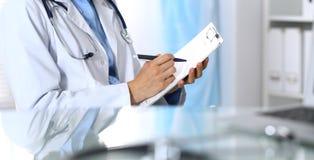 Docteur féminin remplissant vers le haut de la forme médicale sur le presse-papiers, plan rapproché La table en verre se reflétan Photo stock