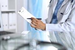 Docteur féminin remplissant vers le haut de la forme médicale sur le presse-papiers, plan rapproché La table en verre se reflétan Photo libre de droits