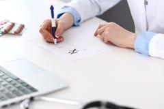 Docteur féminin remplissant vers le haut de la forme de prescription tout en se reposant au bureau en plan rapproché d'hôpital Mé images libres de droits