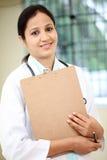 Docteur féminin retenant une planchette photographie stock