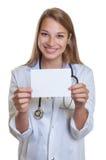 Docteur féminin riant avec les cheveux blonds montrant la carte Photo libre de droits