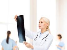 Docteur féminin sérieux regardant le rayon X Image stock