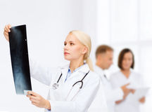 Docteur féminin sérieux regardant le rayon X Image libre de droits