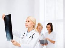 Docteur féminin sérieux regardant le rayon X Photos libres de droits