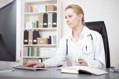 Docteur féminin sérieux Using son ordinateur de bureau Image libre de droits