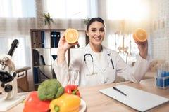 Docteur féminin s'asseyant au bureau dans le bureau avec le microscope et le stéthoscope La femme tient des oranges photos stock