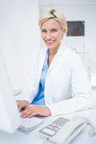 Docteur féminin sûr à l'aide de l'ordinateur dans la clinique Image stock