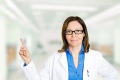 Docteur féminin sûr avec des verres se dirigeant loin avec le doigt images libres de droits