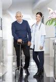 Docteur féminin sûr With Senior Man à l'aide de la canne Photos libres de droits