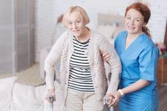 Docteur féminin soigneux aidant son patient plus âgé à marcher Photos stock