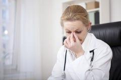 Docteur féminin soumis à une contrainte Holding son pont de nez Photos libres de droits
