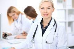 Docteur féminin souriant sur le fond avec le patient et son médecin dans l'hôpital Photo stock