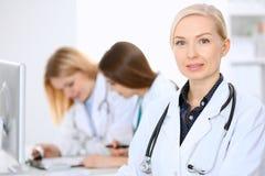 Docteur féminin souriant sur le fond avec le patient et son médecin dans l'hôpital Photo libre de droits