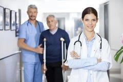 Docteur féminin Standing With Colleague et de patient dos supérieur dedans Photographie stock libre de droits