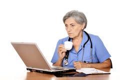 Docteur féminin supérieur avec l'ordinateur portable Photos stock