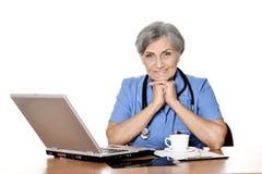 Docteur féminin supérieur avec l'ordinateur portable Photo stock