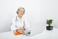 Docteur féminin supérieur réfléchi avec l'ordinateur portable au bureau dans la clinique Photographie stock libre de droits