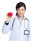 Docteur féminin tenant la boule de forme de coeur Photo libre de droits