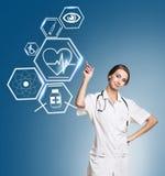 Docteur féminin travaillant avec des icônes de soins de santé Image stock