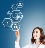 Docteur féminin travaillant avec des icônes de soins de santé Photos libres de droits