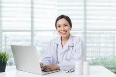 Docteur féminin travaillant avec l'ordinateur portable au bureau et au sourire Image stock