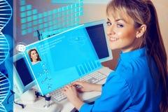 Docteur féminin travaillant dans un coffret à l'ordinateur et au sourire photographie stock libre de droits