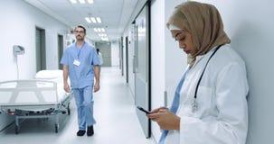 Docteur féminin utilisant le smartphone dans le couloir 4k d'hôpital banque de vidéos