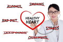 Docteur féminin vérifiant un symbole de coeur Photographie stock