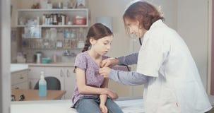 Docteur féminin vérifiant une jeune fille malade banque de vidéos