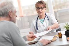 Docteur f?minin donnant la prescription ? son patient photos libres de droits