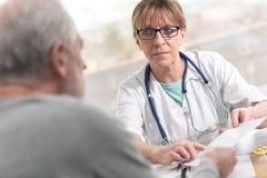Docteur f?minin donnant la prescription ? son patient images stock