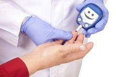 Docteur faisant l'essai de sucre de sang. Visage souriant Images libres de droits