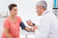 Docteur faisant l'essai à son patient Image libre de droits
