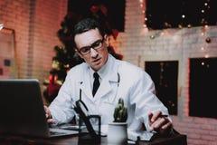Docteur fatigué dans l'uniforme dans le bureau la soirée du Nouveau an photo stock
