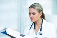 Docteur féminin assez jeune Is Studying Photographie stock