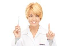 Docteur féminin attirant avec le thermomètre Image libre de droits