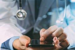 Docteur futé travaillant avec le smartphone dans l'hôpital photographie stock libre de droits